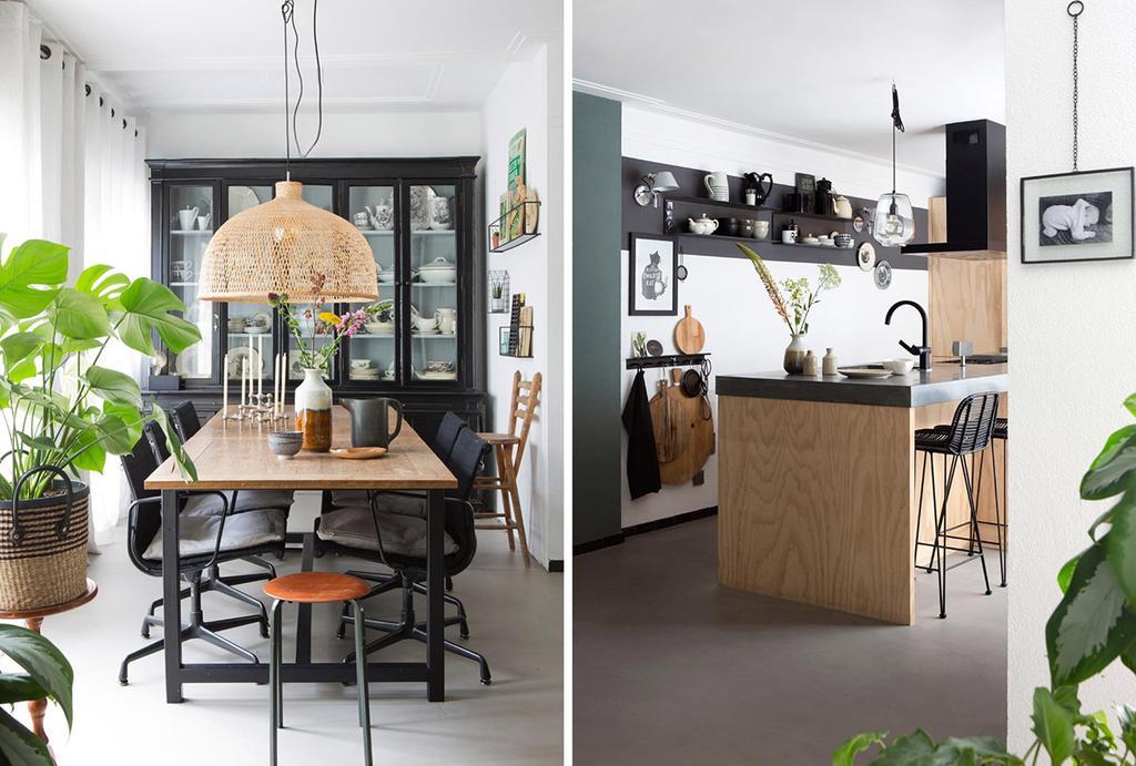Eethoek met een houten eettafel, zwarte buffetkast en groot keukeneiland