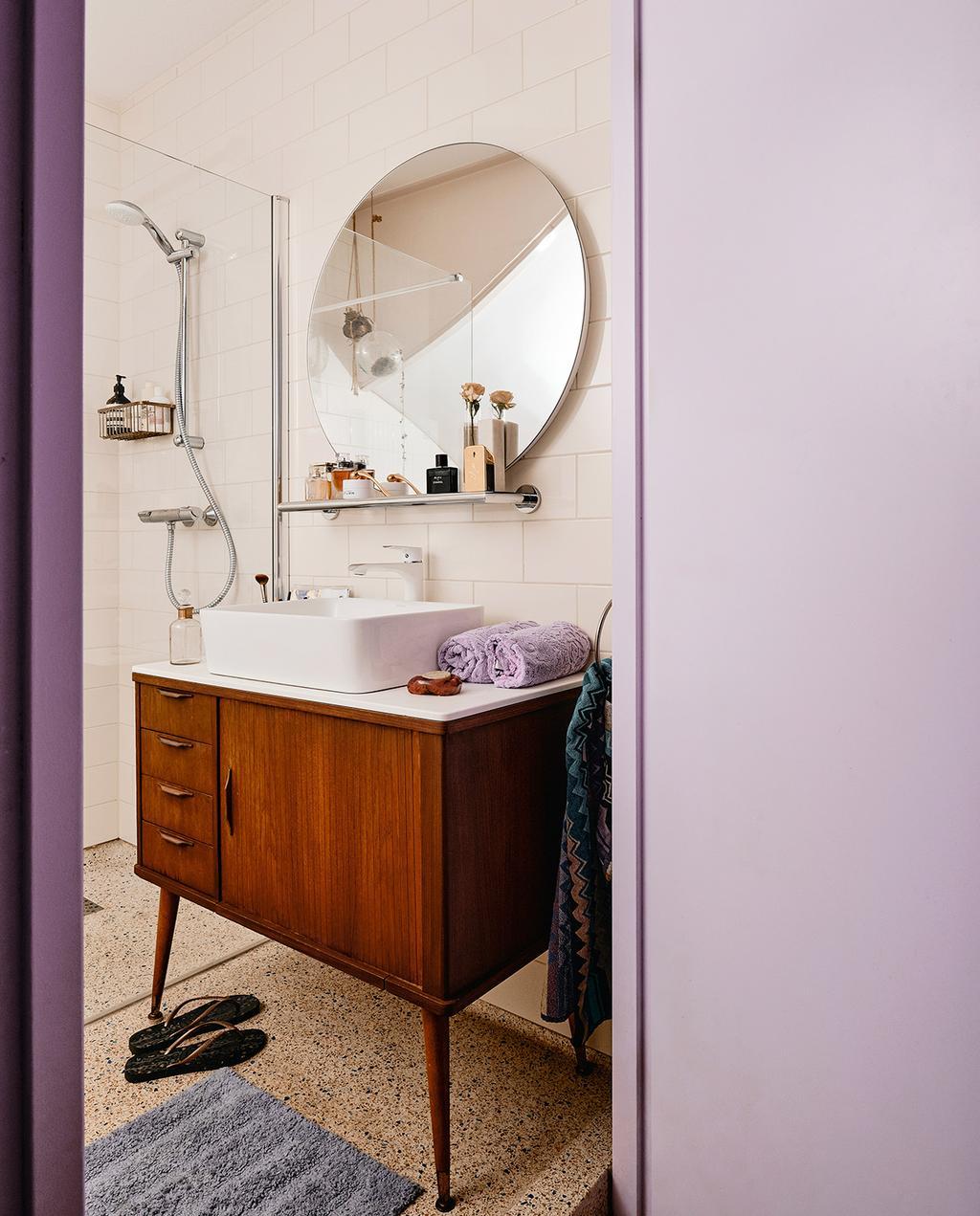 vtwonen 06-2021 | badkamer met een lila muur en een houten wastafelmeubel en ronde spiegel