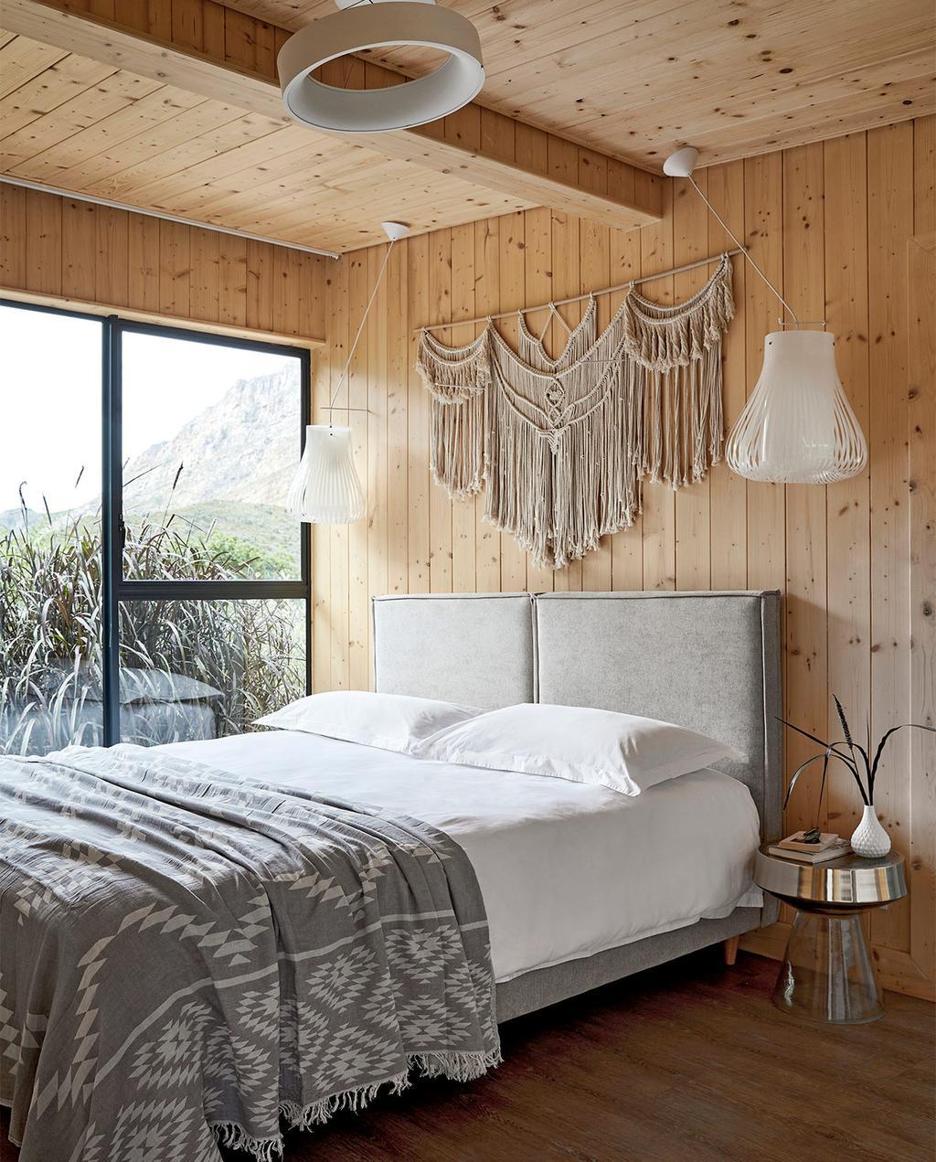 vtwonen special zomerhuizen 07-2021   opgemaakt bed met houten wandplaten, en grijs dekbedovertrek