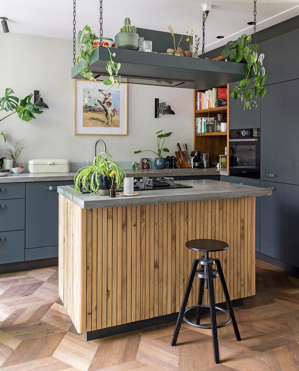 vtwonen 04-2020 | donker grijze keuken met hout accenten en zwarte barkruk Amsterdam