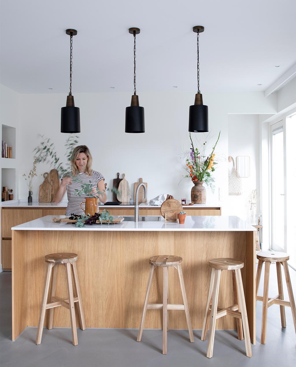 vtwonen 08-2021 | keukeneiland met houten barkrukken en zwarte hanglampen