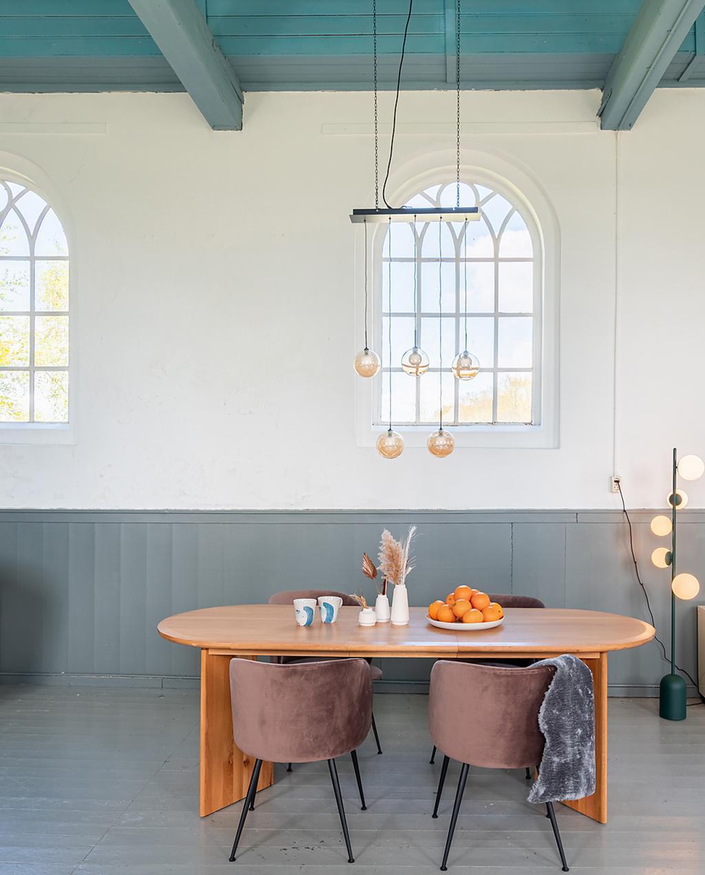 heilige nachten en made.com | overnachten in een opgeknapte kerk | eikenhouten ovalen eettafel omringd door roze fluwelen stoelen