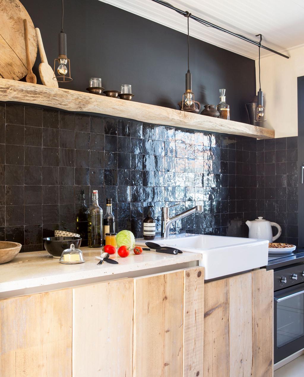 vtwonen binnenkijken special 07-2021 | binnenkijken in een vissershuis | keuken met lichthouten keukenkastjes, zwarte tegels, een licht houten wandplank en zwarte verf.