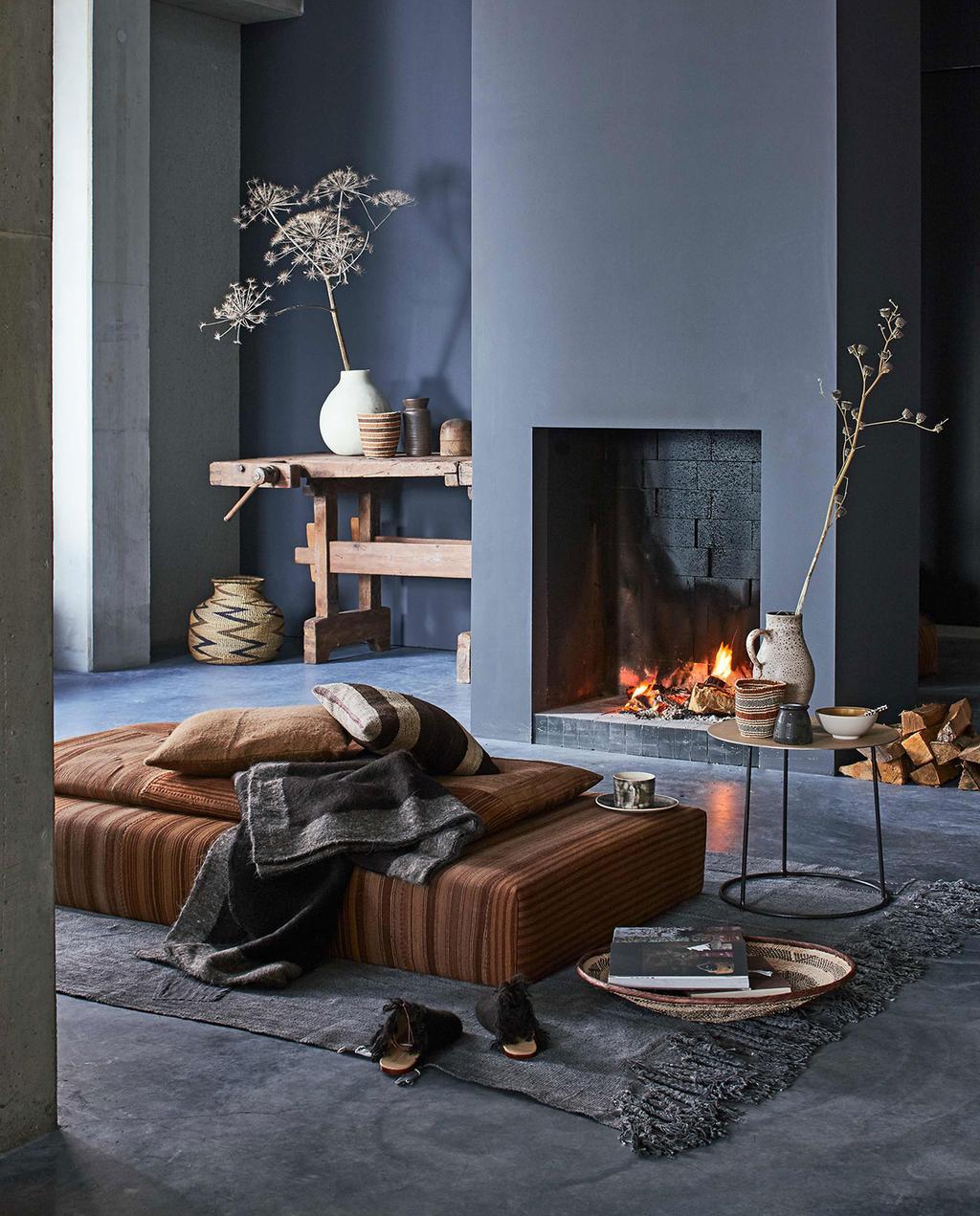 vtwonen 01-2017 | aardetinten woonkamer met brandende open haard op achtergrond, daybed bekleed met alpacawol