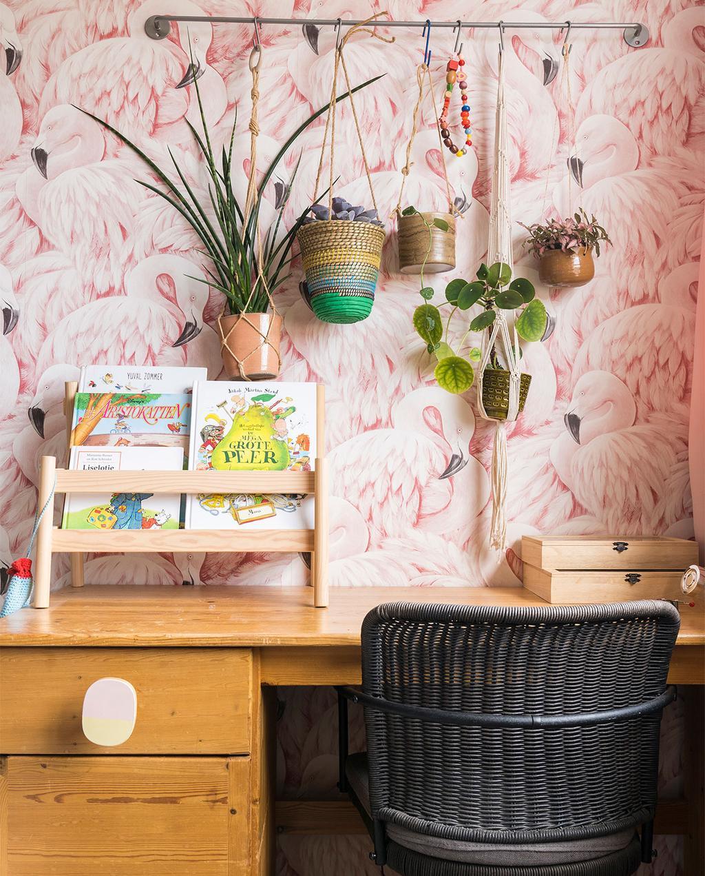 vtwonen 07-2021 | een bureau met een zwarte rieten stoel, met flamingo bloemetjes behang en kinderboeken