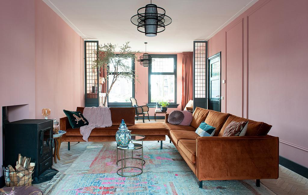 vtwonen 03-2021   woonkamer terracotta bank met roze muur en blauw vloerkleed