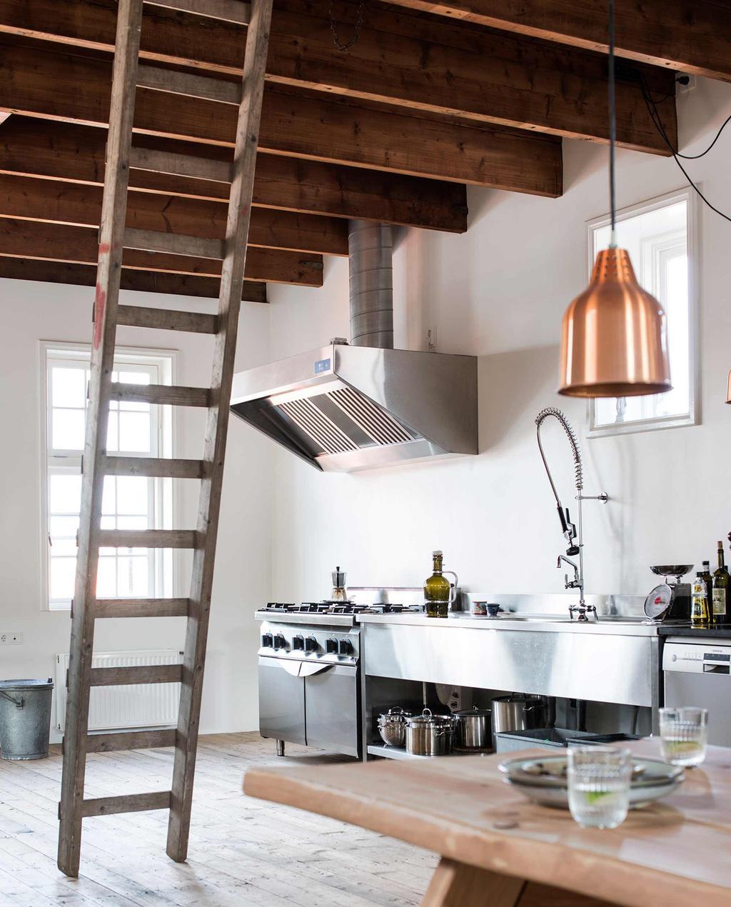 boerenkeuken met metalen apparatuur, veel hout en een ladder