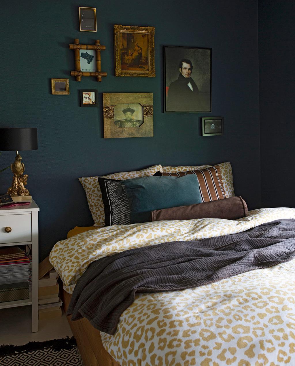 vtwonen 06-2021 | dekbedovertrek met panterprint en verschillende portret kunstwerken achter het bed
