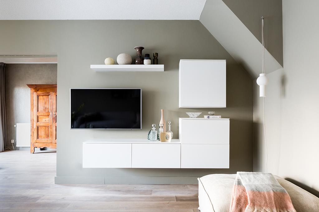 Tv hoek met witte wandkasten en vazen