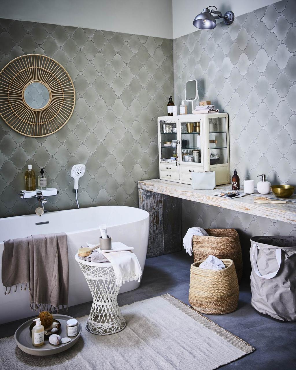 Een badkamer met bad en lichte tegels op de muur