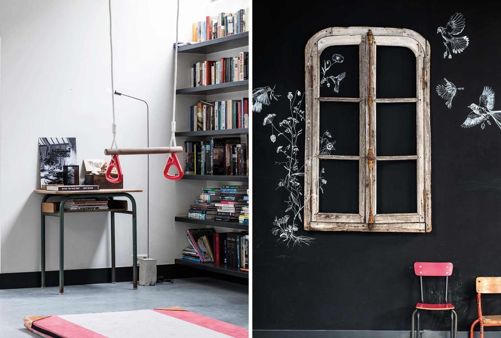 Oud raam tegen een zwarte wand en een boekenkast met vintage gymringen