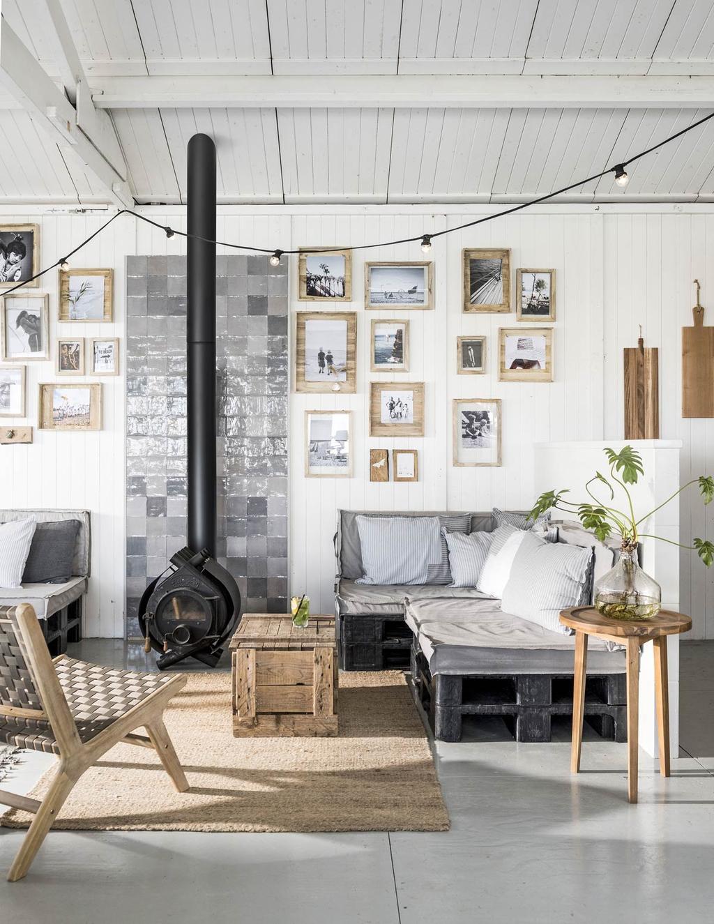 Loungehoek met zwarte haard en houten fotolijstjes bij Ajuma