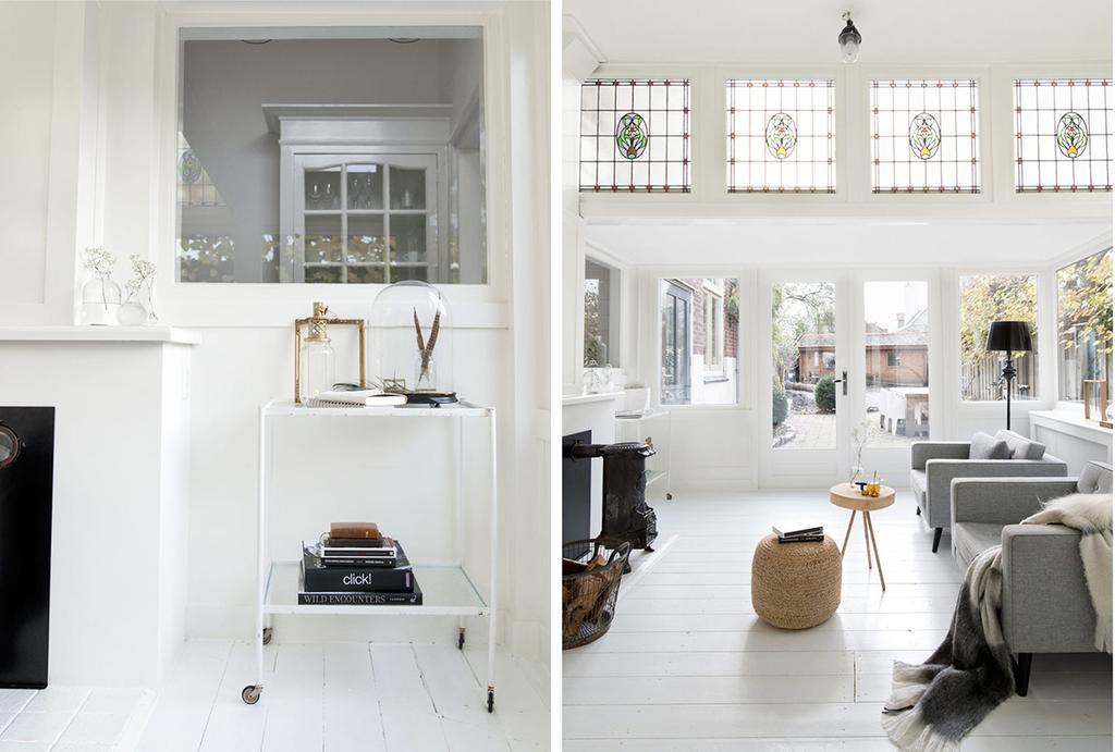 Witte woonkamer met glas-in-lood ramen en een witte trolley