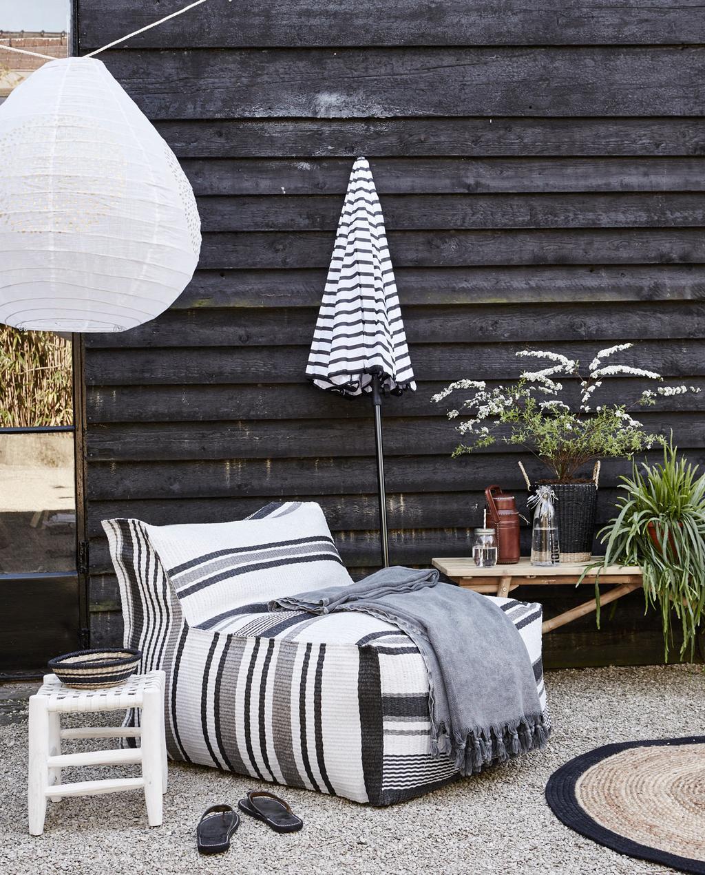 Maak je balkon en terras zomerklaar. Zwart-witte tuin met stoelpoef en gestreepte parasol | vtwonen