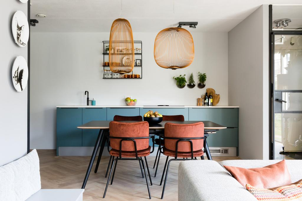Blauwe keuken met eethoek, met zwarte eettafel en rode stoelen