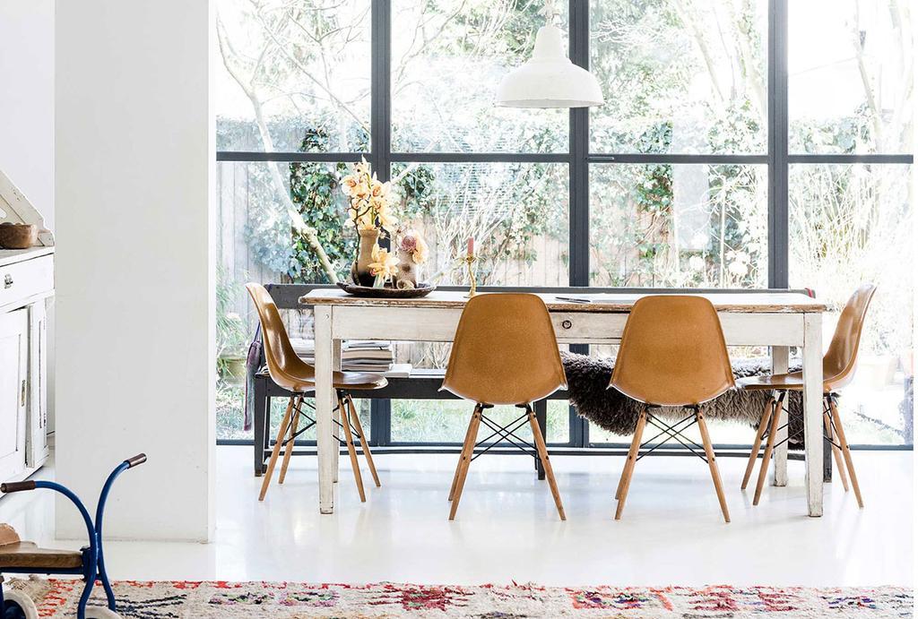 Witte vloer met houten eettafel en Vitra stoelen