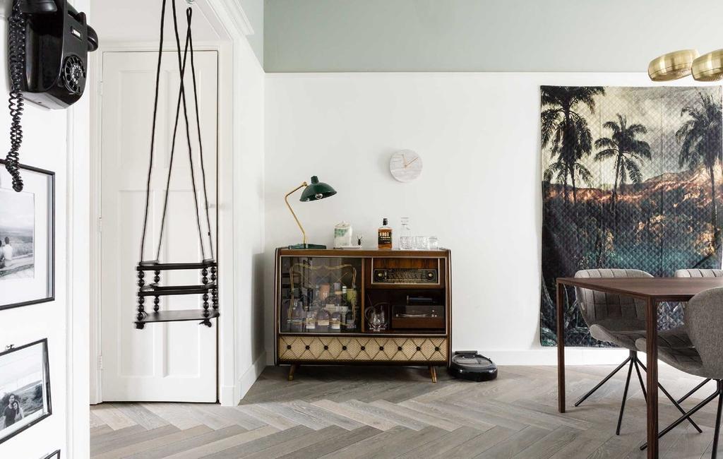 vtwonen | antieke kast als drankkast in woonkamer met groot tropisch wandkleed
