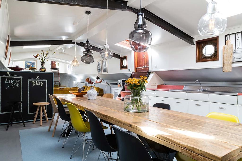 Weer verliefd op je huis make-over woonboot met een lange eettafel en glazen hanglampen