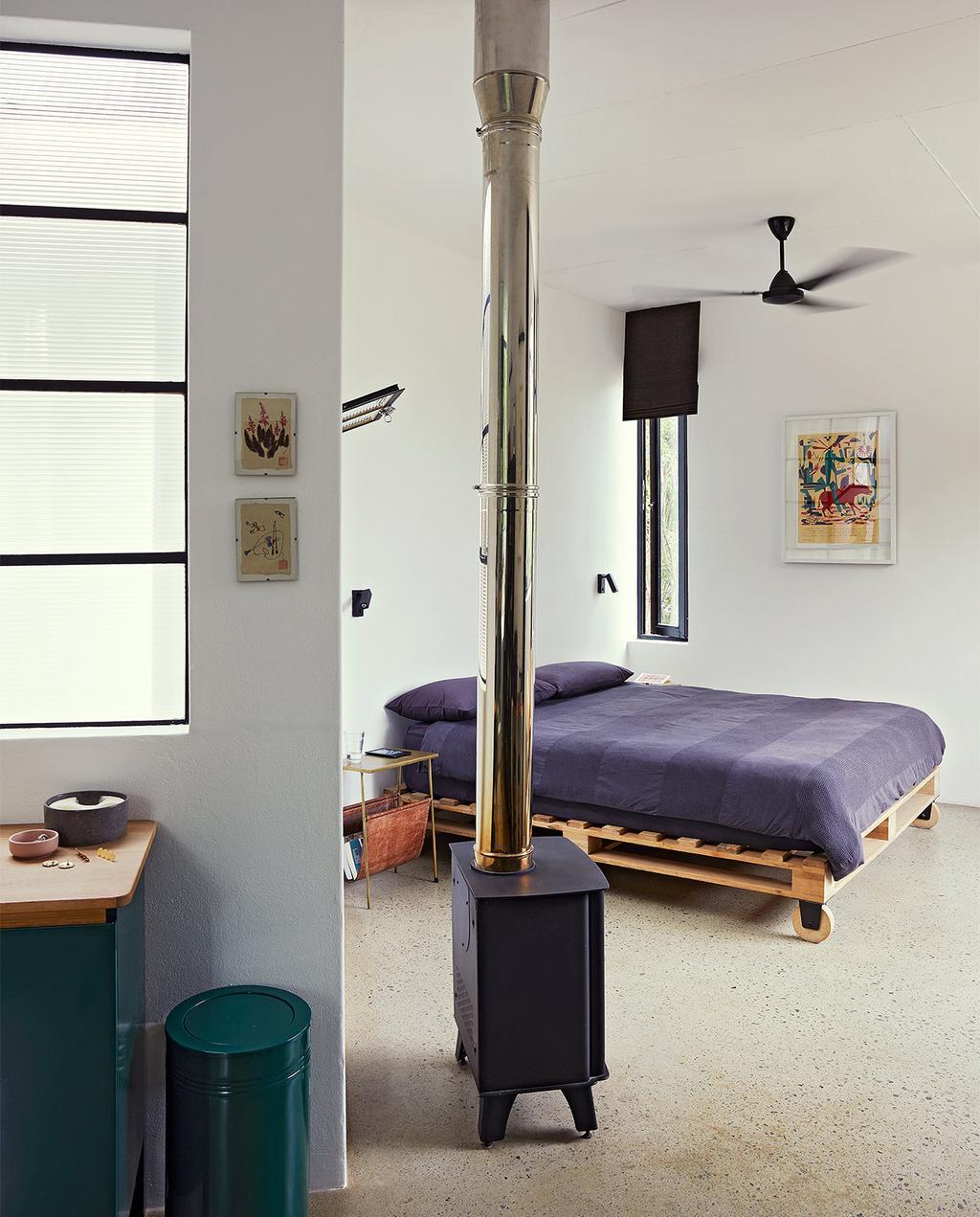 vtwonen binnenkijk special 07-2021 | slaapkamer met pallet bed en kachel met een betonnen vloer
