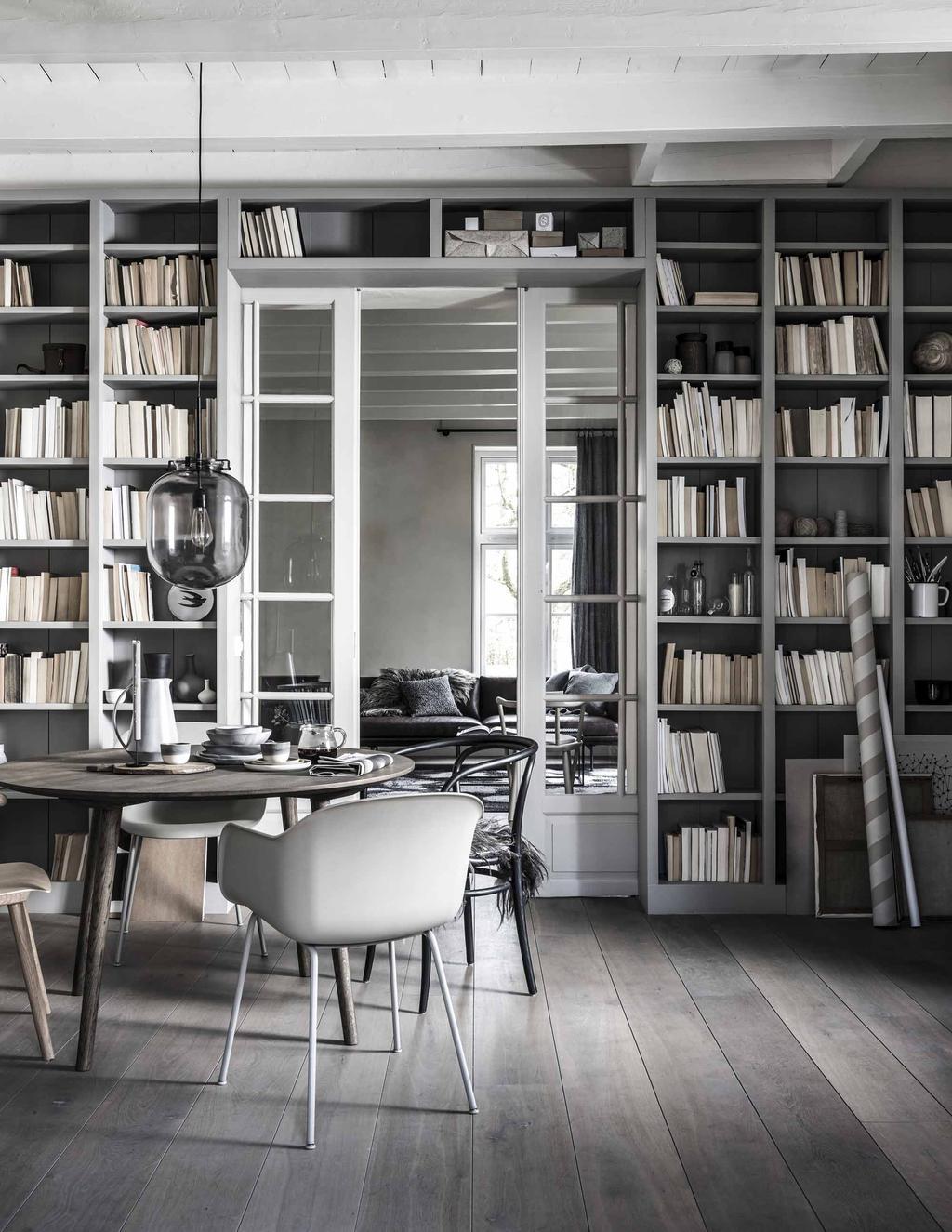 Een wandboekenkast met een ronde eettafel en stoelen in verschillende tinten grijs