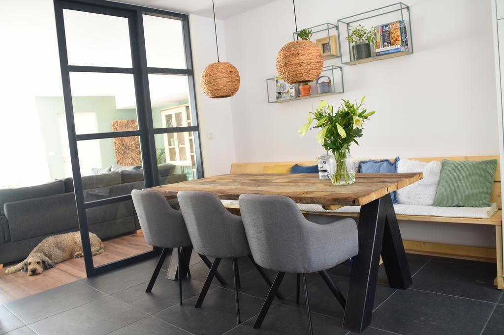 onze-favoriete-plek-voor-een-ontbijtje-en-een-kop-koffie-grove-tafel-met-stalen-poten-en-grijze-stoelen-met-staal-als-tegenhanger-aan-de-andere-kant-een-gezellige-bank-met-kussens-en-dekens-industriele-deuren-kan-de-keuken-afsluiten-van-de-kamer