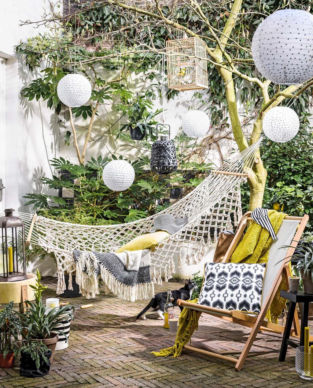Maak je balkon en terras zomerklaar. kleine tuin met klimop, lampionnen en macrame hangmat | vtwonen