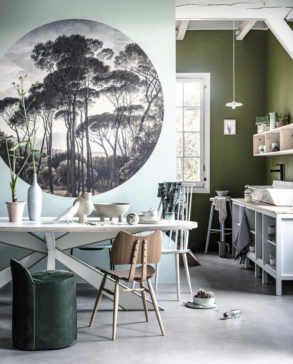 een houten eettafel dat zich in een groene eetkamer bevindt