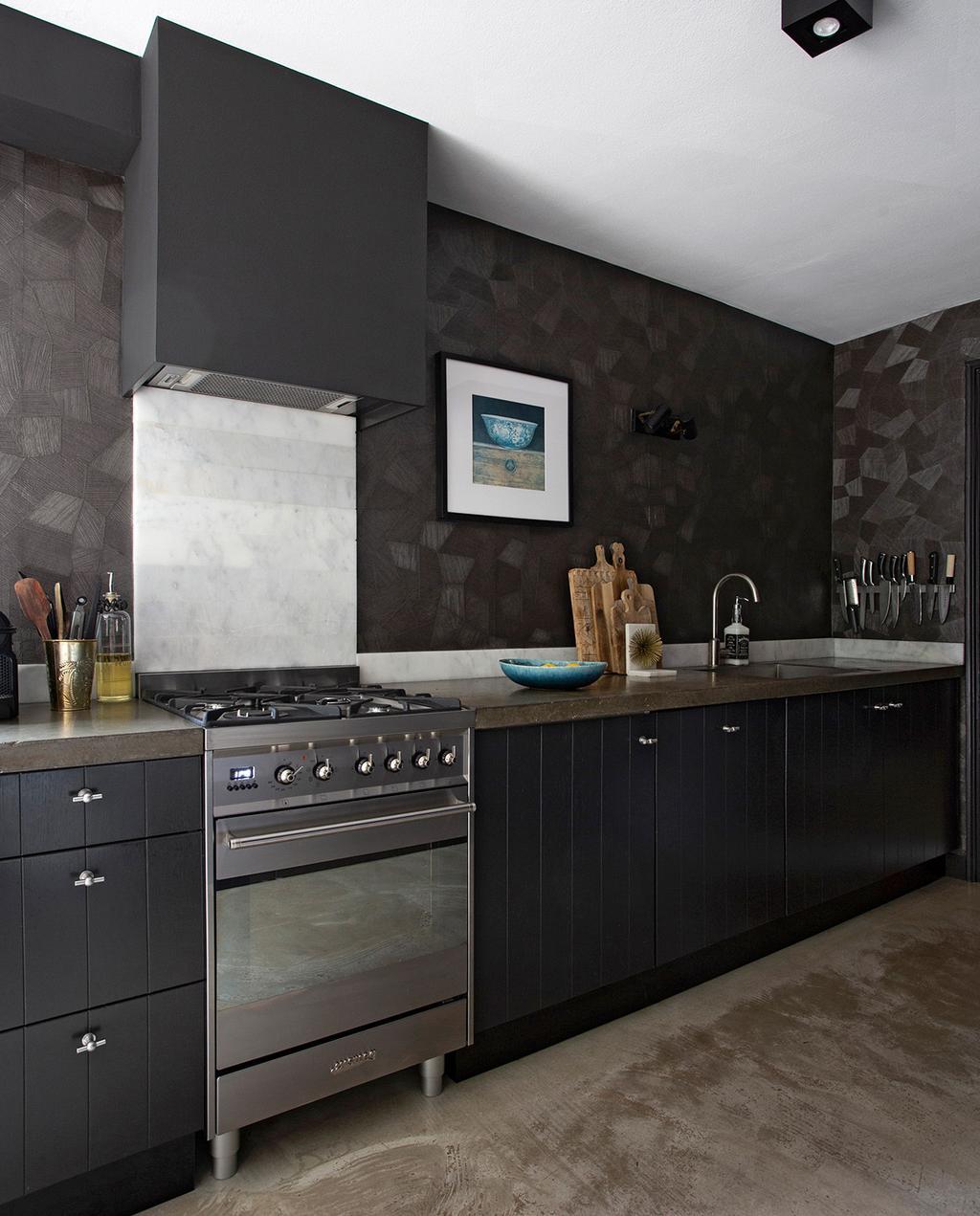 vtwonen 06-2021 | zwarte keuken met zilver fornuis en reliëf werk op de muur