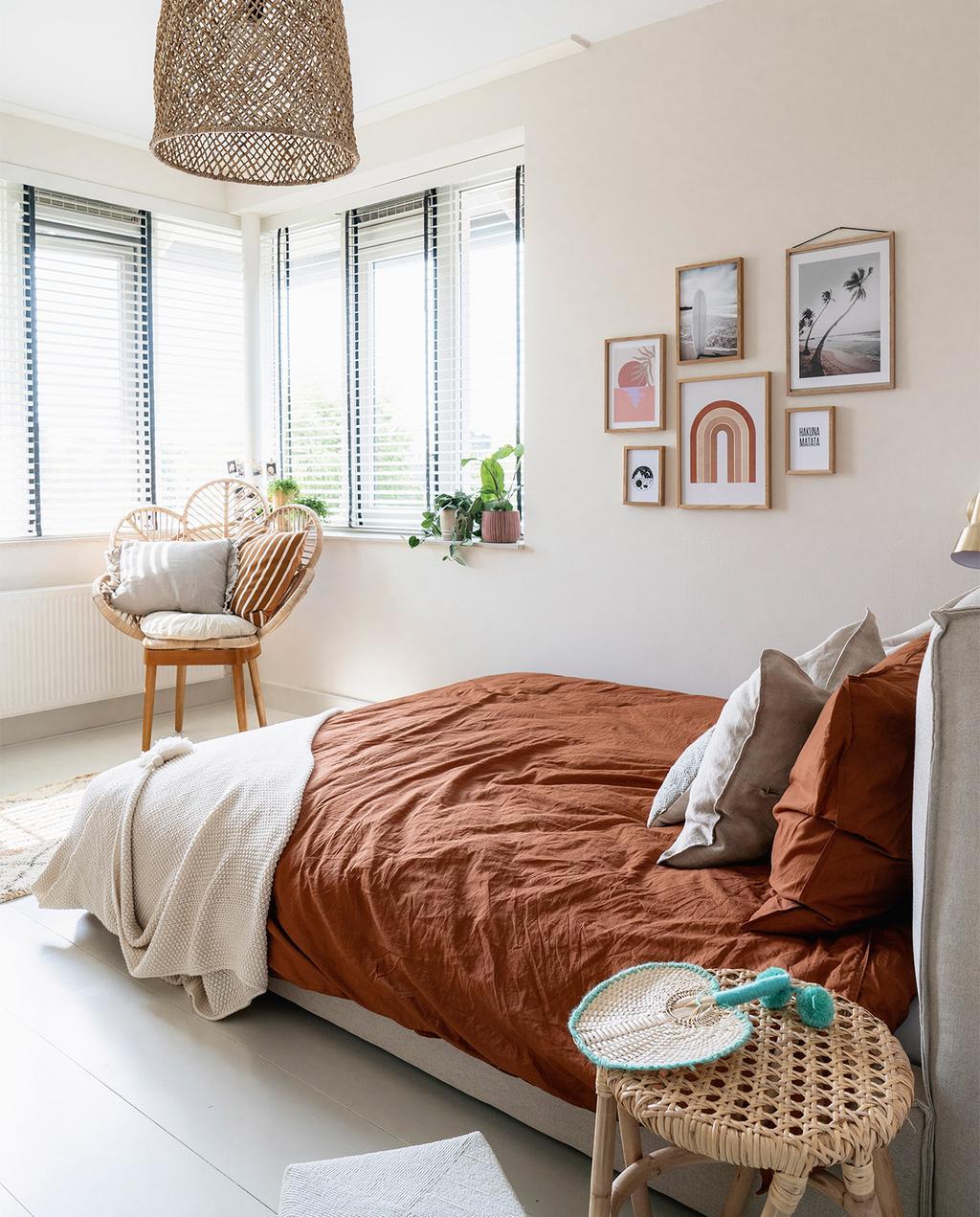 vtwonen 08-2021 | tienerkamer met bed en terracotta dekbedovertrek, op de achtergrond zijn verschillende posters