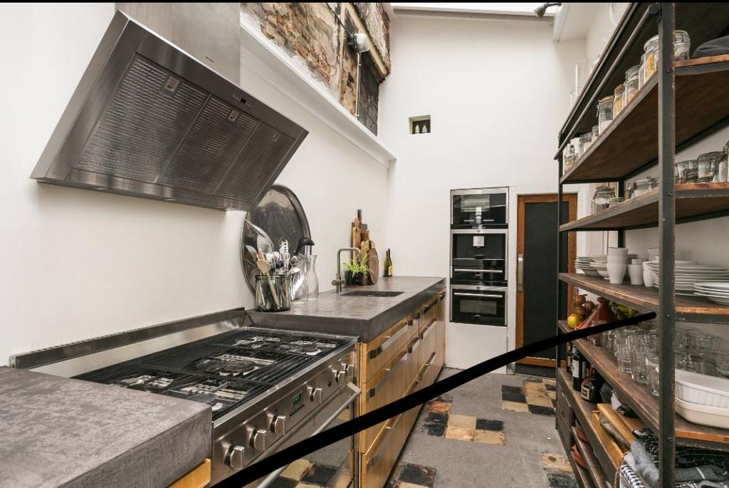 het-aanrechtblad-is-betonlook-de-koelkast-en-de-inbouwapperatuur-zitten-weggewerkt-in-de-muur-koelkast-achter-het-schoolbord