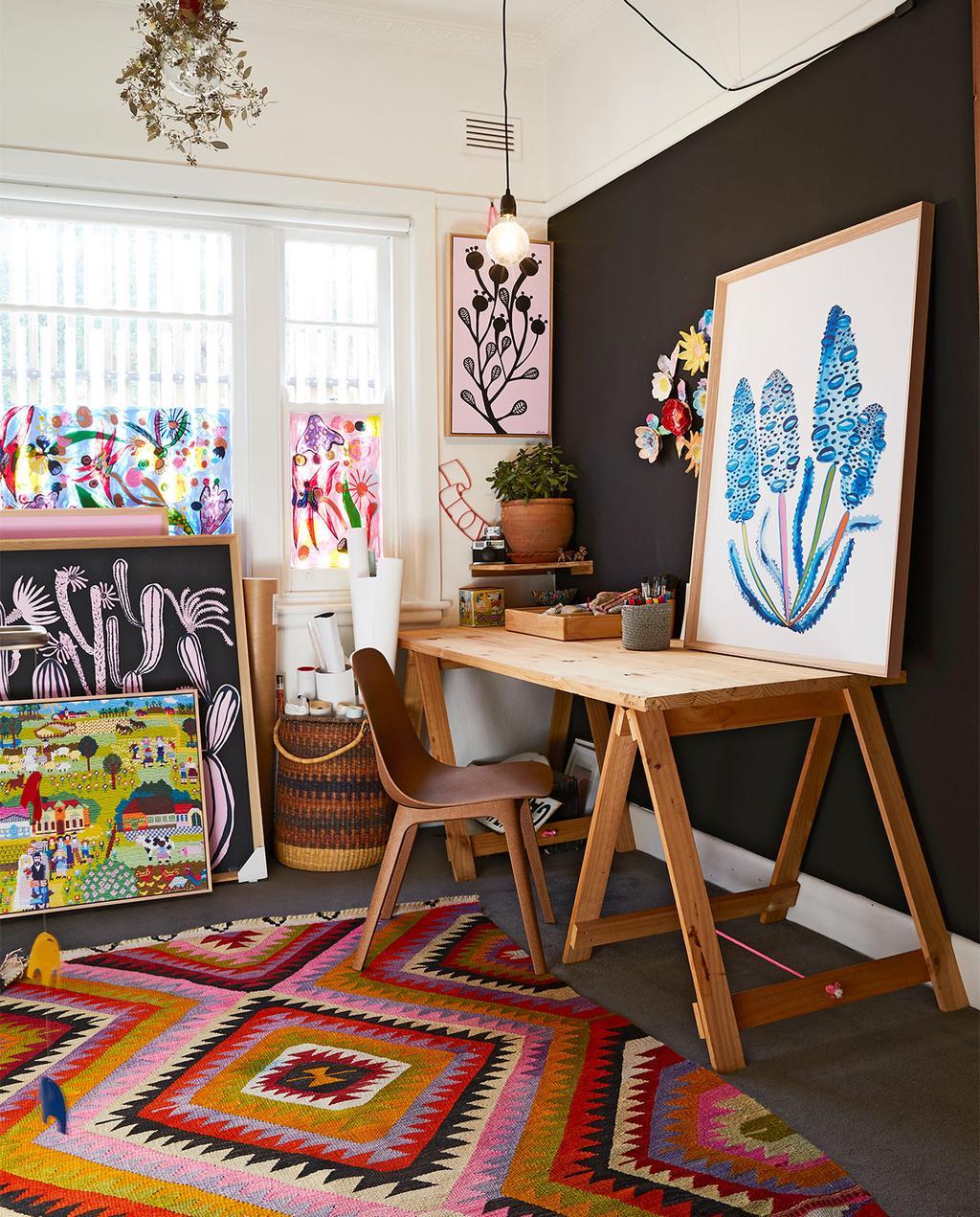 vtwonen binnenkijk special zomerhuizen 07-2021 | bureau in de werkkamer in Melbourne met een kleurrijk vloerkleed met patronen en veel verschillende kunstwerken staand tegen de muur