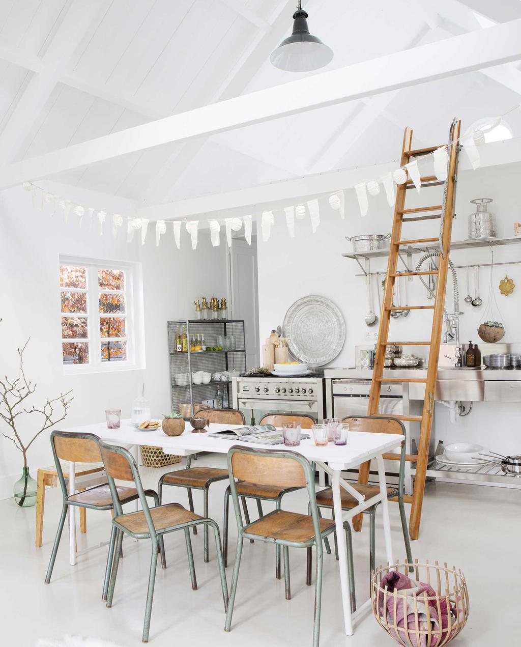 witte keuken met vintage stoelen en houten ladder