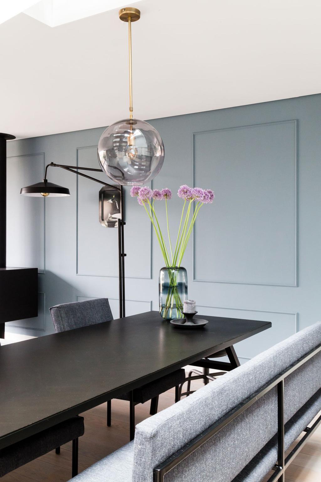 Zwarte eettafel, lamp, grijze eetkamerbank, blauwe muur