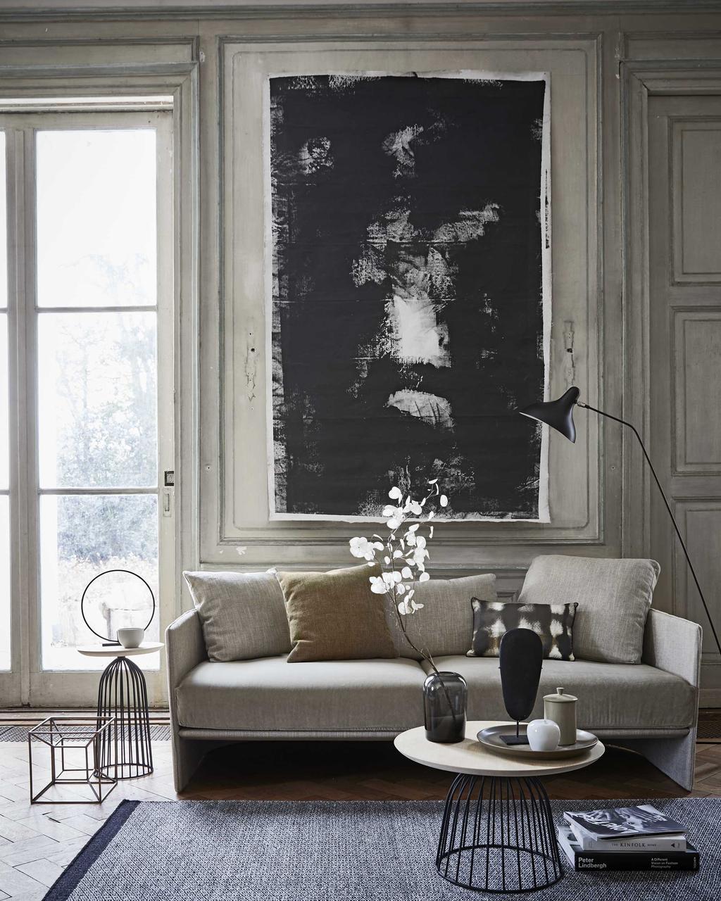 Woonkamer in de tinten grijs en zwart met schilderij voor kunst in huis