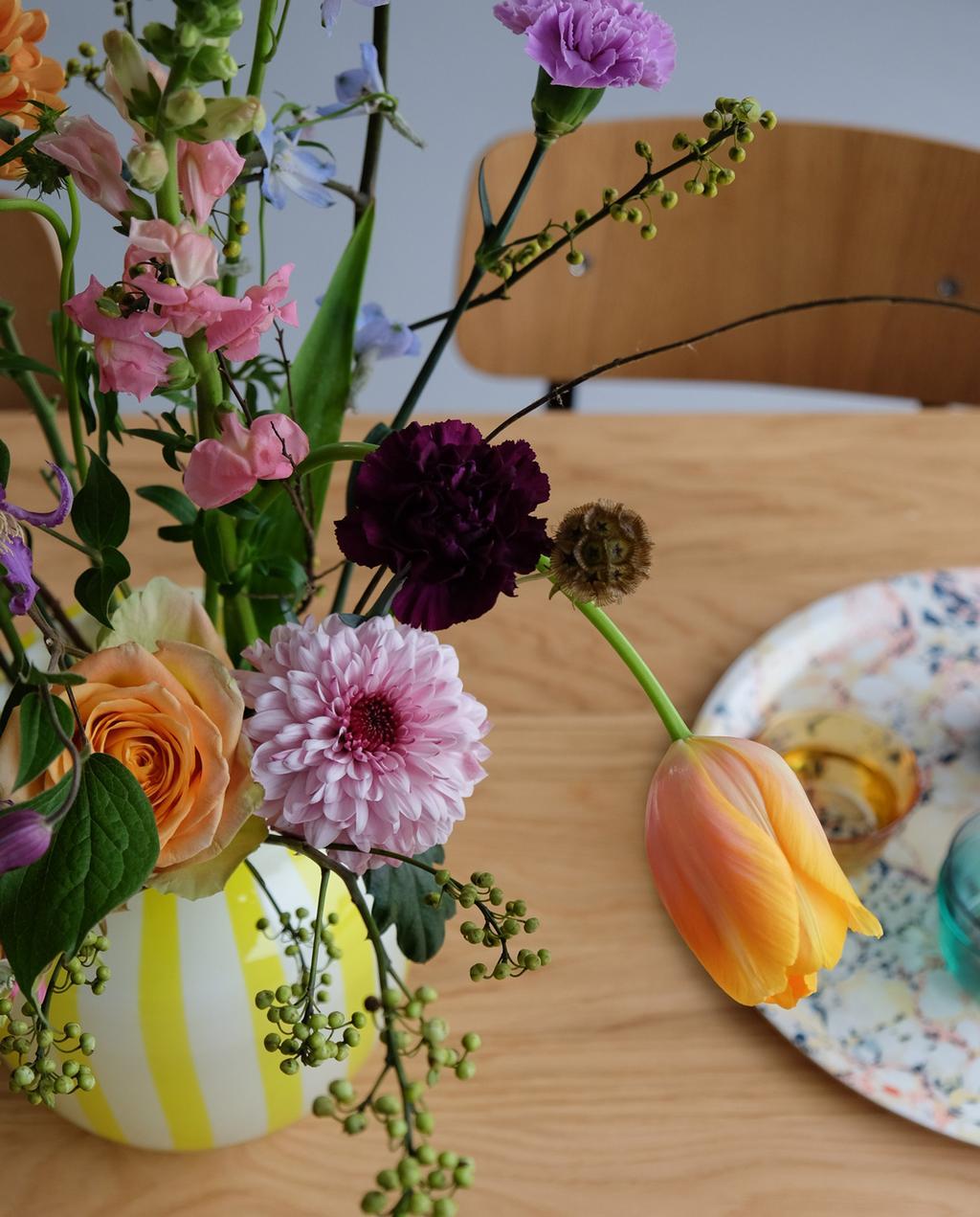 geel en wit gestreepte vaas van hay met bloemen
