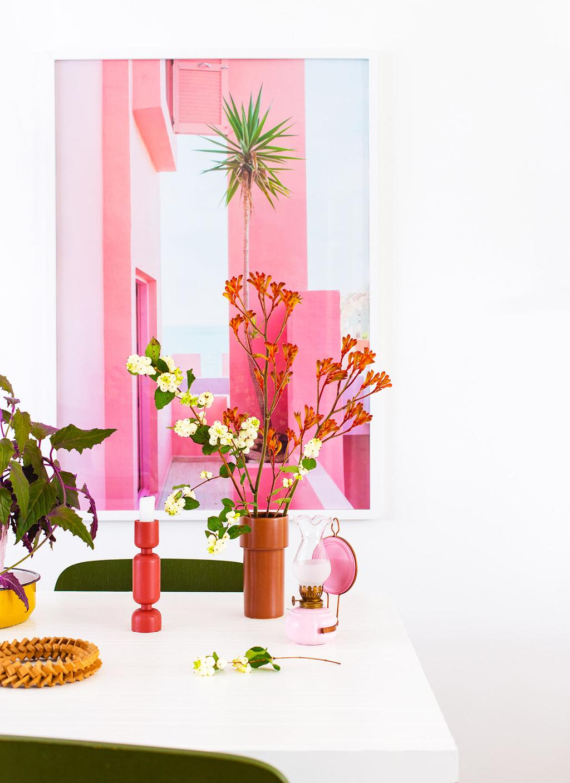 Roze olielamp op tafel bij Oh Marie! met een roze poster van WOWN! op de achtergrond