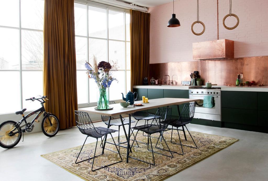 Voormalig bedrijfspand met een groene keuken en koperen keukenwand