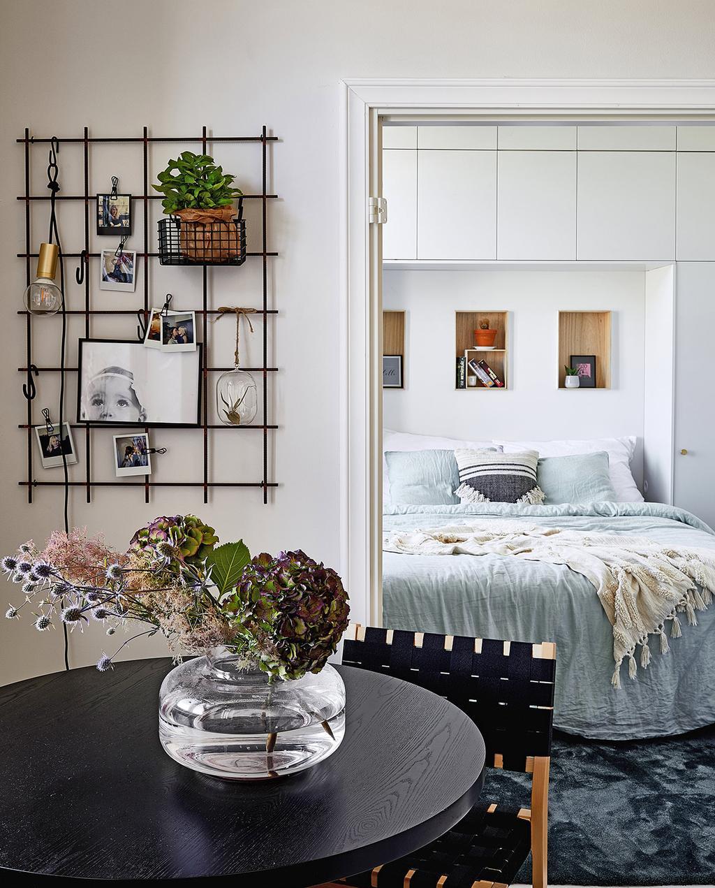 vtwonen special tiny houses | zicht op deur naar de slaapkamer met wandrek en foto's