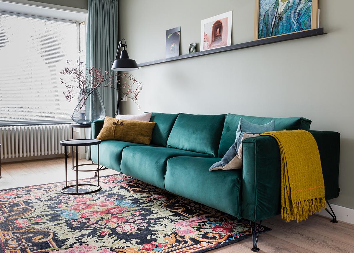 Woontrend voorjaar funky folkore felgekleurd tapijt groene bank okergele plaid