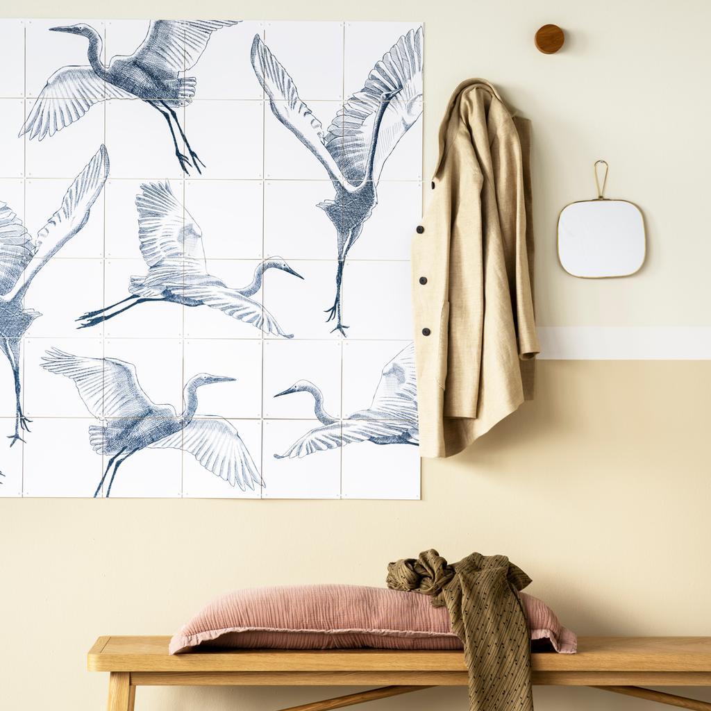Happy Days 2021 kraanvogels aan muur met gele jas aan de kapstok en een houten bankje op de grond