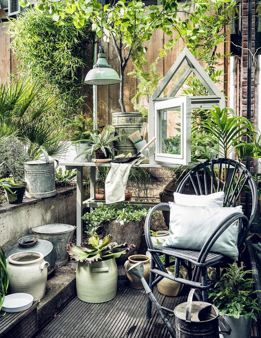 Balkon styling met zwarte rotan tuinstoel en tuinkas