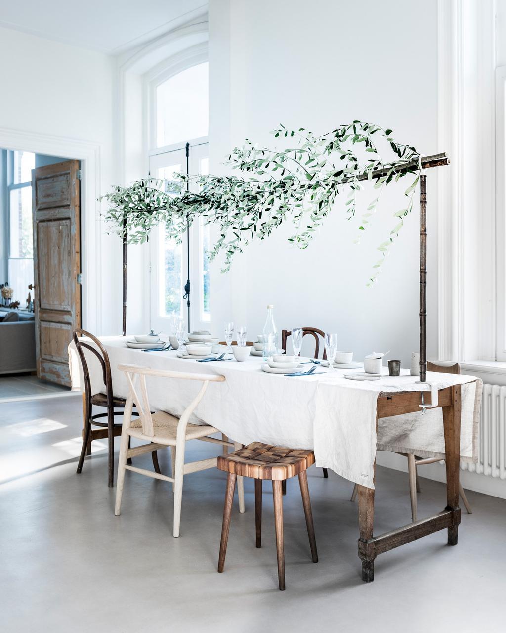 Feestelijke tafelschikking met wit, traditioneel laken en maretakken