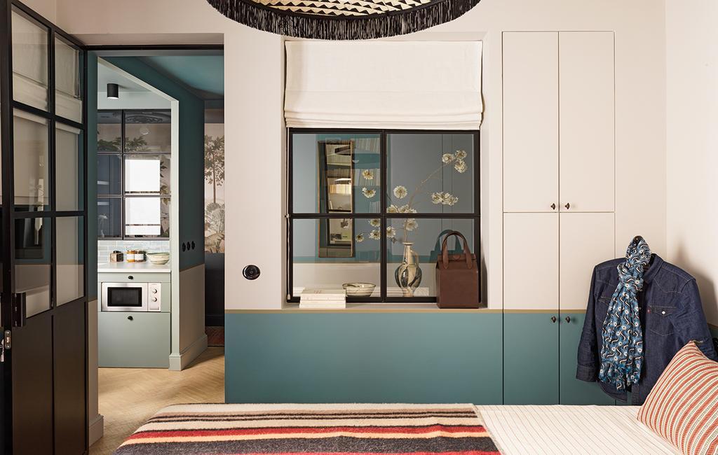vtwonen special tiny houses | scheiding tussen de slaapkamer en de keuken met een glazen wand en een groene lambrisering op de muren