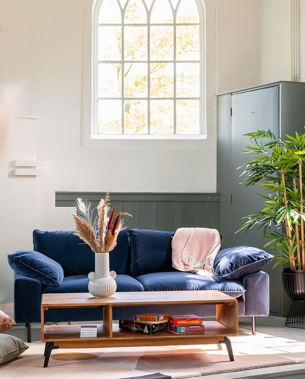heilige nachten en made.com | overnachten in een opgeknapte kerk | donkerblauwe fluwelen bank en houten salontafel bij groot raam