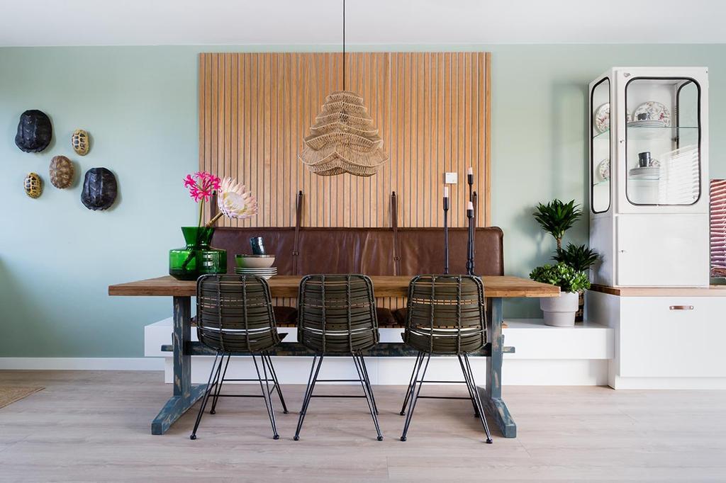 Weer verliefd op je huis: eethoek met een houtpaneel en leren zitkussen tegen de groene wand