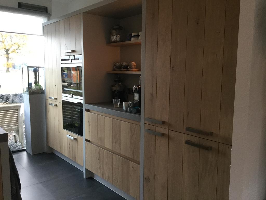 nieuwe-keuken-met-massief-eiken-gewithed-waste-fronten-de-stollen-zijn-lichtgrijs-met-een-keramiekaanrechtblad-in-betonlook-en-blinde-grepen-aan-de-linkerkant-de-apparatenkast-rechts-heeft-gedeeltelijke-robuuste-rechthoekige-grepen-ontwerp-is-van-mij-de-fronten-zagen-we-in-een-keukenshowroom