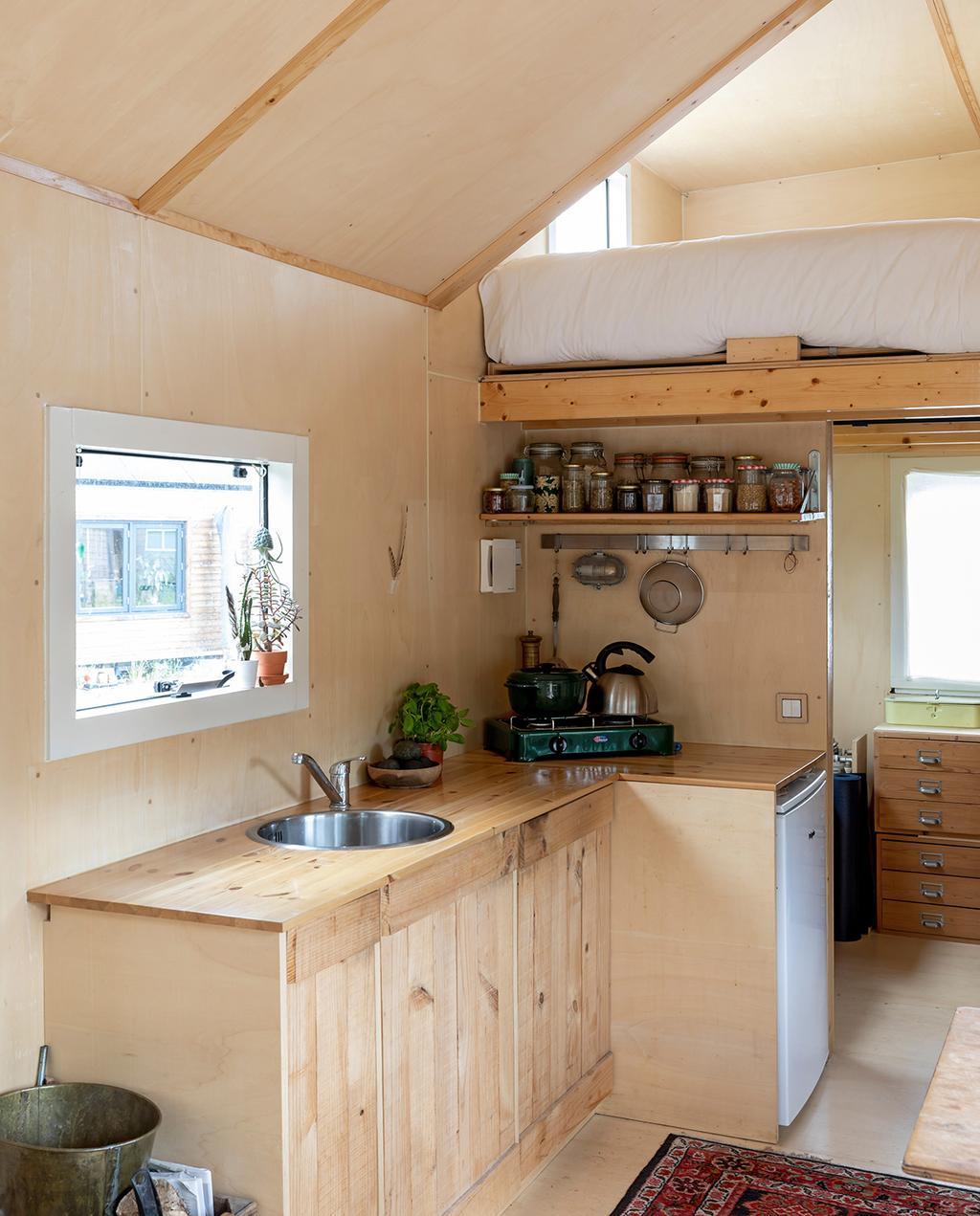 vtwonen special tiny houses | zelfvoorzienend keukenblok met Perzisch tapijt op vloer en hoogslaper
