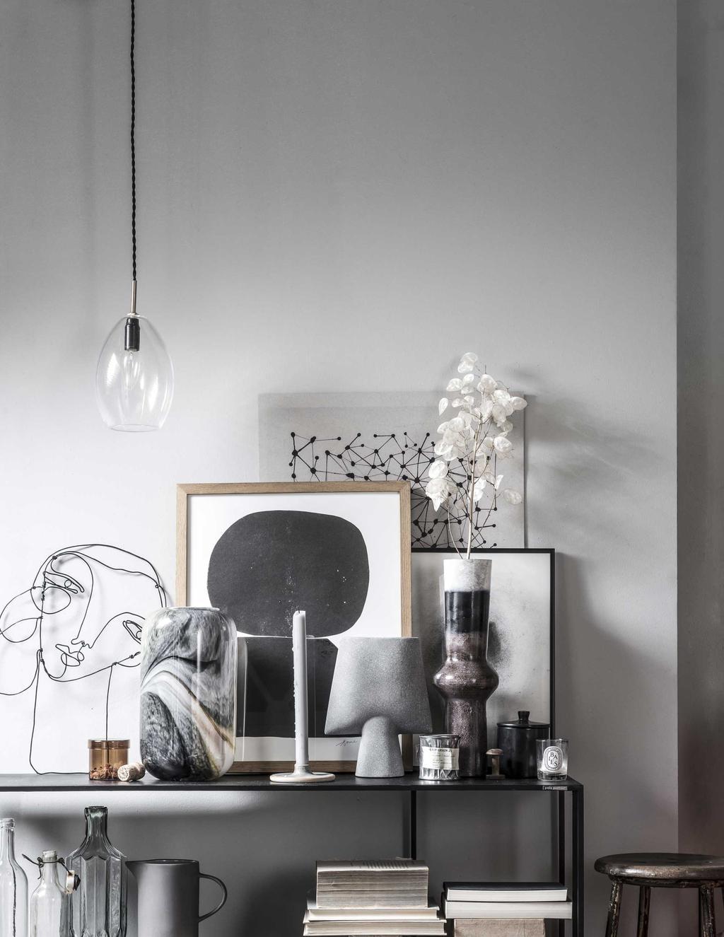 Een zwarte tafel met kunst en vazen in verschillende tinten grijs