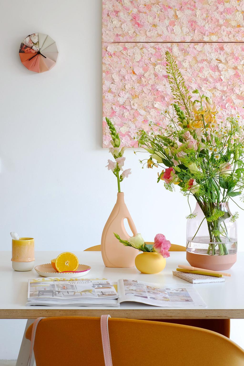 Design eethoek met roze schilderij en een boeket op tafel