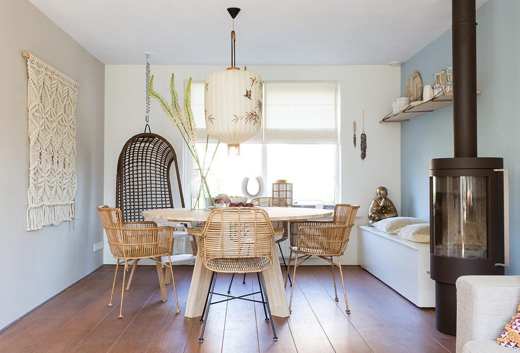 Blauwe eethoek met houten ronde tafel en rotan hangstoel